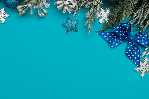Winter holiday decoration card festive concept: christmas trees, stars, pines on blue background with copy space