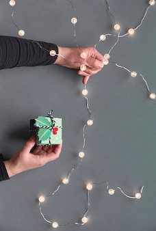 Winter holiday festive composition. hand holding ceramic fir tree decoration. new year or christmas flat lay.