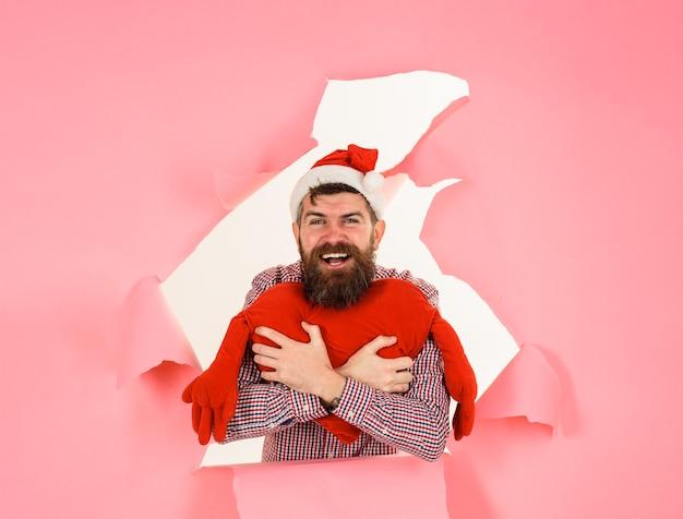 Зимний праздник шоппинг улыбающийся санта-мужчина с подушкой в форме сердца смотрит через дыру на рождество