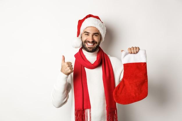 冬の休日とお祝いのコンセプト。贈り物と親指を立てるためにクリスマスの靴下を見せて、満足して笑って、白い背景の上に立って幸せな男