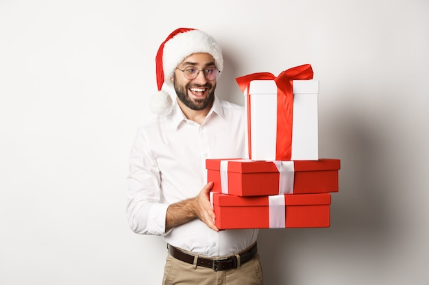 冬の休日とお祝い。幸せな男はクリスマスプレゼントを持ってきて、贈り物を持って、サンタの帽子をかぶって、立っています