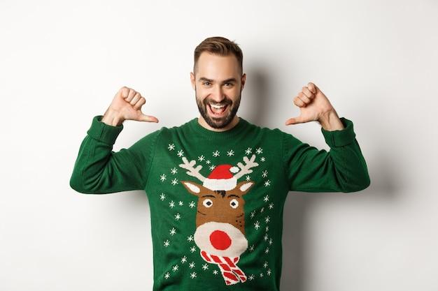 겨울 방학과 크리스마스. 열정적으로 보이는 자신감 있는 청년, 자랑스럽게 자신을 가리키며 흰색 배경 위에 서 있는