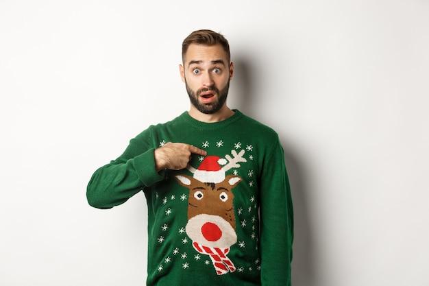겨울 방학과 크리스마스. 혼란스러운 수염 난 남자가 자신을 가리키며 제안에 깜짝 놀라 흰색 배경 위에 스웨터를 입고