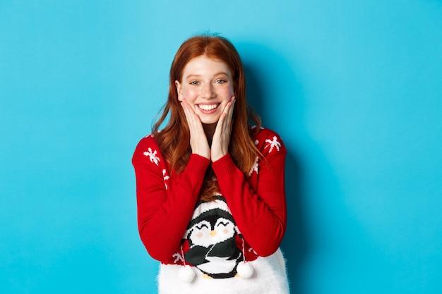 冬の休日とクリスマスイブのコンセプト。愛らしい赤毛の女の子が赤面して頬に触れ、カメラを感謝して幸せに見つめ、青い背景にクリスマスセーターに立っています。