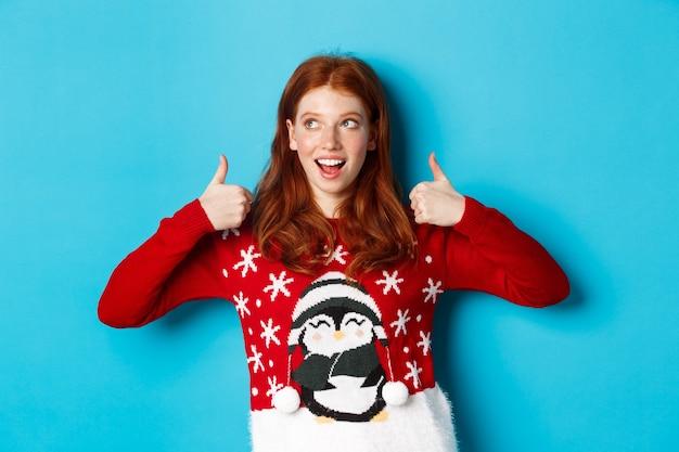 冬の休日とクリスマスイブのコンセプト。クリスマスセーターの美しい赤毛の女の子、新年を祝って、親指を上に表示し、左上隅、青い背景を見ています。