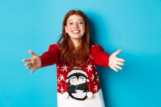 Зимние каникулы и концепция сочельника. красивая рыжая девушка в рождественском свитере тянется к объятиям, протягивает руки для объятий и улыбается, стоя в свитере на синем фоне.