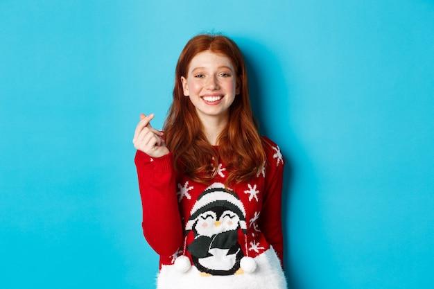 冬の休日とクリスマスイブのコンセプト。クリスマスセーターでかわいい笑顔の赤毛の女の子、ハートのサインを表示し、青い背景の上に立って、新年あけましておめでとうございます。