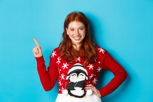겨울 방학 및 크리스마스 이브 개념입니다. 빨간 물결 모양의 머리를 가진 귀여운 10대 소녀, 왼쪽 위 모서리를 가리키고 카메라를 보며 웃고, 파란색 배경 위에 서 있습니다.