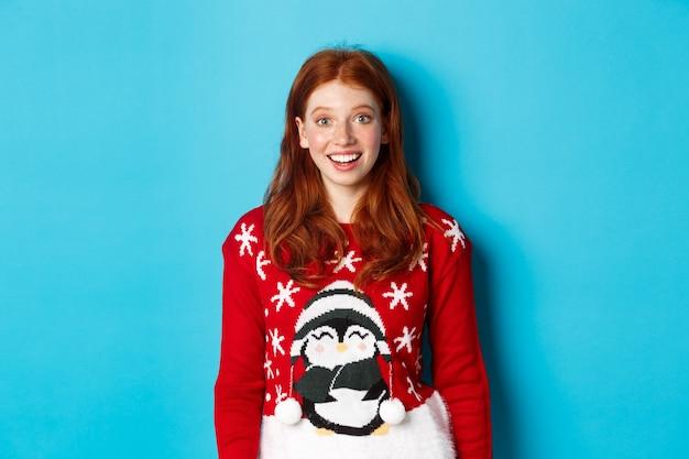 겨울 방학 및 크리스마스 이브 개념입니다. 크리스마스 스웨터를 입은 흥분된 빨간 머리 소녀가 파란색 배경에 서서 카메라를 보고 놀랐습니다.