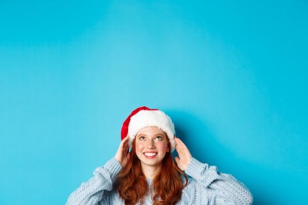 겨울 방학 및 크리스마스 이브 개념. 산타 모자에 귀여운 빨간 머리 소녀의 머리, 바닥에서 나타나고 파란색 배경 위에 서있는 로고를보고, 복사 공간에서 찾고.