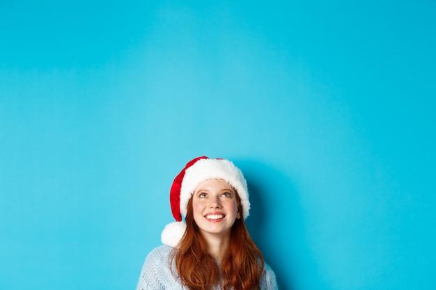 겨울 방학 및 크리스마스 이브 개념입니다. 산타 모자를 쓴 귀여운 빨간 머리 소녀의 머리는 아래에서 나타나 복사 공간을 올려다보고 로고를 쳐다보고 파란색 배경 위에 서 있습니다.
