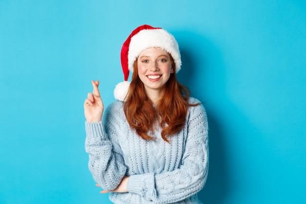 겨울 방학 및 크리스마스 이브 개념입니다. 산타 모자를 쓴 희망적인 빨간 머리 소녀, 크리스마스에 소원을 빌고, 행운을 위해 손가락을 교차하고, 파란 배경 위에 서서 웃고
