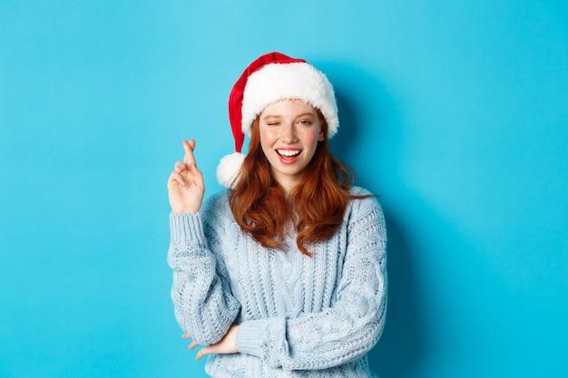 冬の休日とクリスマスイブのコンセプト。サンタの帽子をかぶった希望に満ちた赤毛の女の子、クリスマスに願い事をし、幸運とウインクのために指を交差させ、青い背景の上に立っています。