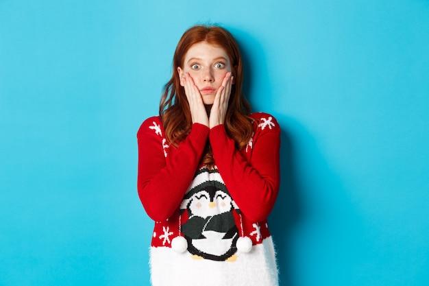 겨울 방학 및 크리스마스 이브 개념입니다. 감동하고 말문이 막힌 빨간 머리 소녀는 헐떡거리고, 믿을 수 없다는 표정으로 카메라를 쳐다보고, 파란색 배경에 크리스마스 스웨터를 입고 서 있다