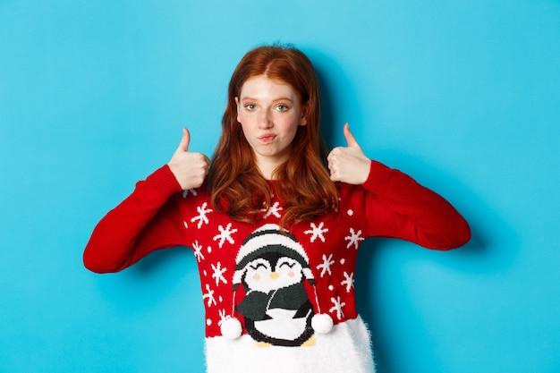 겨울 방학 및 크리스마스 이브 개념입니다. 크리스마스 스웨터를 입은 빨간 머리 소녀, 승인에 고개를 끄덕이고 엄지손가락을 치켜들고, 좋은 제품을 칭찬하고, 파란색 배경 위에 서 있습니다.