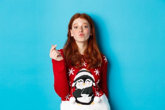 겨울 방학 및 크리스마스 이브 개념입니다. 크리스마스 스웨터를 입은 사랑스러운 빨간 머리 소녀는 파란색 배경 위에 서 있는 키스를 위해 하트 사인과 입술을 보여줍니다.