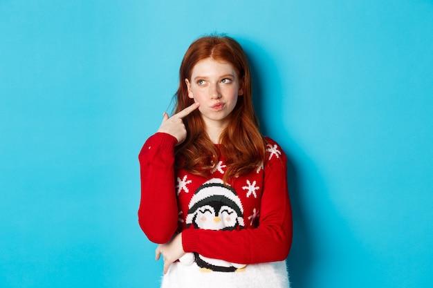 冬の休日とクリスマスイブのコンセプト。クリスマスセーターのかわいい赤毛の女の子、思慮深く、笑顔で頬に触れ、選択を行い、左上隅を見て考え、青い背景。