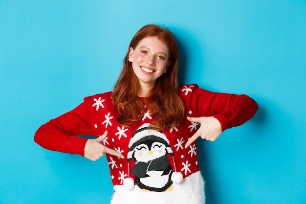 겨울 방학 및 크리스마스 이브 개념입니다. 파란 배경 위에 서 있는 펭귄과 함께 귀여운 크리스마스 스웨터를 손가락으로 가리키는 예쁜 빨간 머리 소녀.