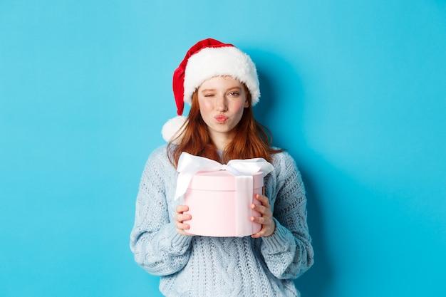 冬の休日とクリスマスイブのコンセプト。セーターとサンタの帽子をかぶった生意気な赤毛の女の子、新年の贈り物を保持し、カメラを見て、青い背景に立っています。