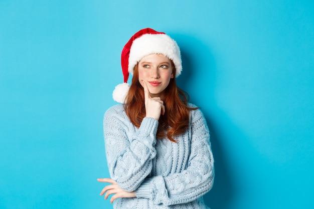 冬の休日とクリスマスイブのコンセプト。そばかす、サンタの帽子をかぶって考え、新年のお祝いを計画し、青い背景の上に立っている愚かな赤毛の女の子