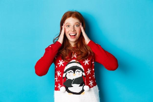 겨울 방학 및 크리스마스 이브 개념입니다. 놀랍고 흥분된 빨간 머리 소녀, 머리에 손을 잡고 파란색 배경 위에 서 있는 크리스마스 선물을 믿을 수 없다는 표정으로 응시합니다.