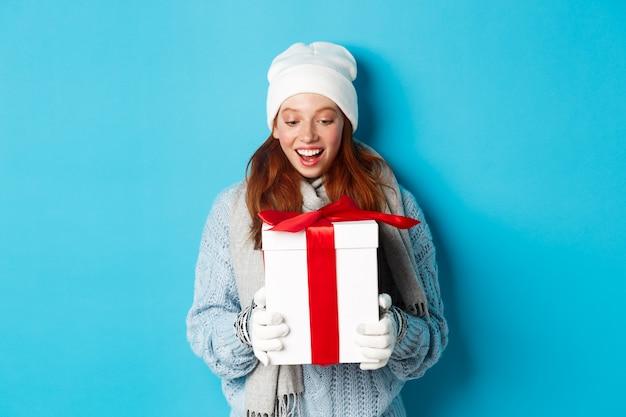冬の休日とクリスマスイブのコンセプト。新年の贈り物を受け取って、青い背景の上に立って、驚いて、現在を見て、ビーニーとセーターで驚いたかわいい赤毛の女の子