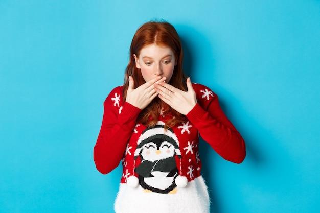 겨울 방학 및 크리스마스 이브 개념. 놀란 빨간 머리 소녀 헐떡이며, 경외감으로 내려다보고, 로고를 쳐다보고, 파란색 배경에 크리스마스 스웨터에 서.