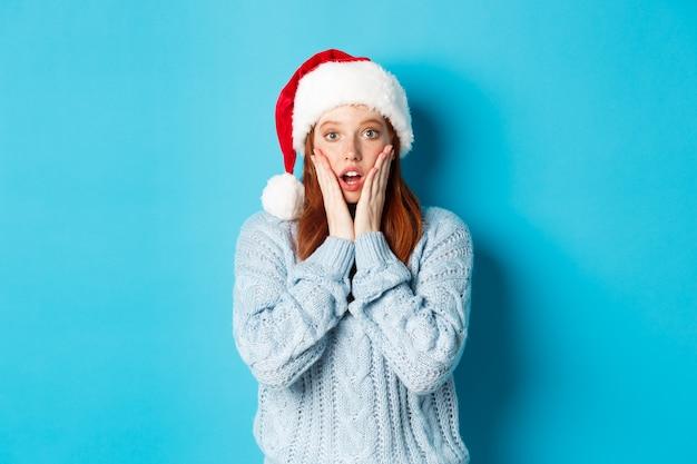 겨울 방학 및 크리스마스 이브 개념입니다. 산타 모자를 쓰고 놀란 빨간 머리 소녀, 카메라를 믿을 수 없다는 표정으로 쳐다보고, 놀란 입을 벌리고, 파란 배경 위에 서 있다