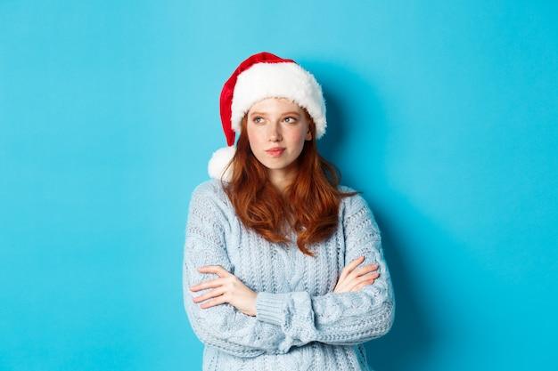겨울 방학 및 크리스마스 이브 개념. 산타 모자와 스웨터에 사려 깊은 빨간 머리 여자, 왼쪽보고 숙고, 크리스마스 계획, 파란색 배경 위에 서.