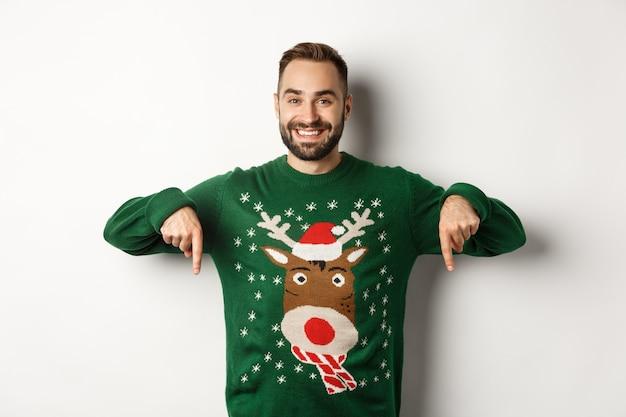 겨울 방학과 크리스마스. 수염을 기른 잘생긴 웃는 남자, 손가락을 아래로 가리키고 프로모션 제안을 보여주고, 녹색 스웨터를 입고, 흰색 배경 위에 서 있습니다.
