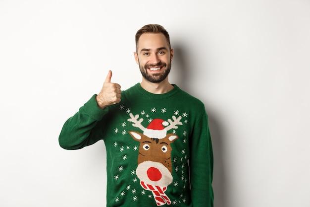 冬休みとクリスマス。何かのように、承認に親指を立てて現れる幸せなひげを生やした男は、白い背景の上に立って、良い仕事を賞賛します。