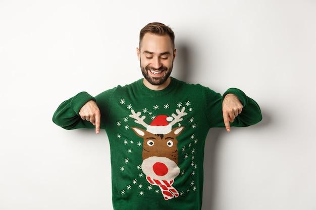 겨울 방학과 크리스마스. 녹색 스웨터를 입은 행복한 백인 남자, 손가락을 아래로 가리키고 만족스러운 표정, 흰색 배경 위에 서 있는