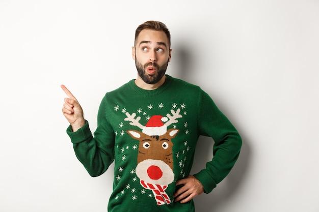Зимние каникулы и рождество. человек смотрит с любопытством на новогоднее торговое промо, стоя в забавном свитере на белом фоне.