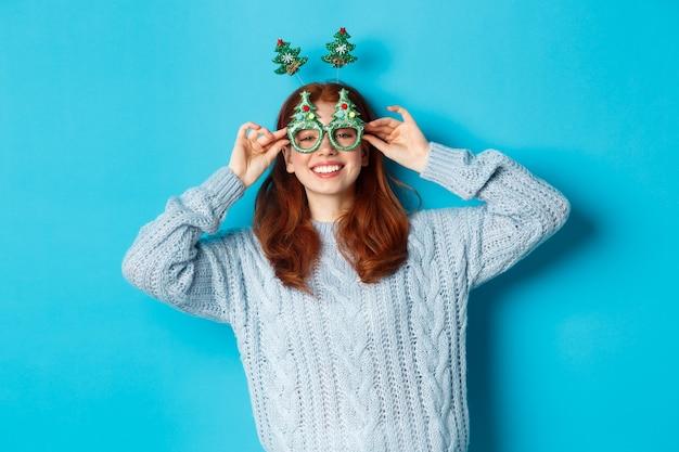 겨울 방학 및 크리스마스 판매 개념. 새 해를 축 하, 재미있는 파티 머리 띠와 안경, 웃 고 바보, 파란색 배경을 입고 아름 다운 빨간 머리 여성 모델.