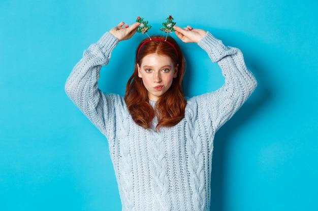 冬休みとクリスマスの販売コンセプト。新年を祝う美しい赤毛の女性モデル、面白いパーティーのヘッドバンドとセーターを着て、カメラに微笑んでいます。