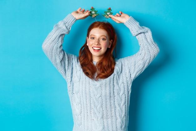 冬休みとクリスマスの販売コンセプト。新年を祝う美しい赤毛の女性モデル、面白いパーティーのヘッドバンドとセーターを着て、カメラに笑顔