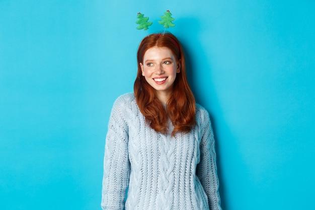 겨울 방학 및 크리스마스 판매 개념. 웃 고, 파란색 배경 위에 서있는 로고에서 왼쪽보고 재미있는 새 해 머리 띠에 귀여운 빨간 머리 소녀.