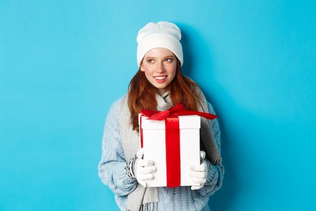 겨울 방학 및 크리스마스 판매 개념. 흰색 비니와 장갑에 서, 크리스마스 선물을 들고 왼쪽 찾고, 생각, 파란색 배경 위에 서 사려 깊은 빨간 머리 여자.
