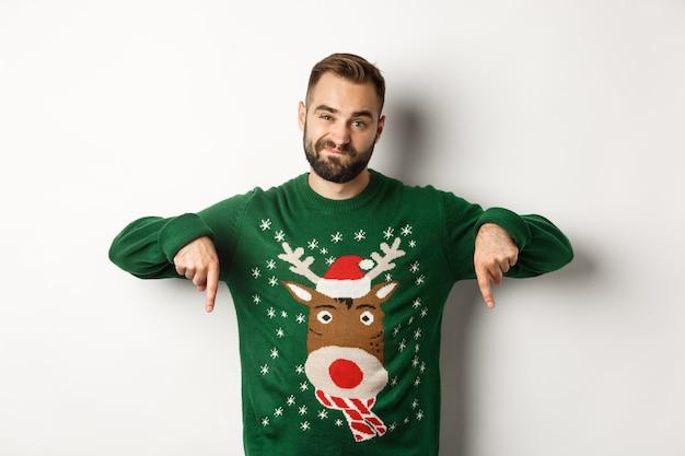 겨울 방학과 크리스마스. 흰색 배경 위에 서서 프로모션이 싫어서 손가락을 아래로 가리키며 실망한 표정을 짓고 있는 회의적인 수염 난 남자