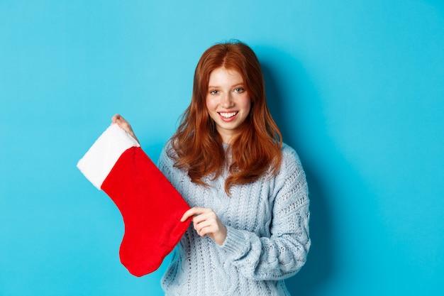 冬の休日とギフトのコンセプト。クリスマスの靴下と笑顔を示し、新年を祝って、青い背景の上に立っているセーターのかわいい赤毛の女の子。