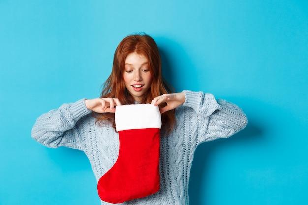 冬の休日とギフトのコンセプト。クリスマスの靴下の中を見て、幸せそうに笑って、クリスマスプレゼントを受け取り、青い背景に立っている面白い赤毛の女の子。