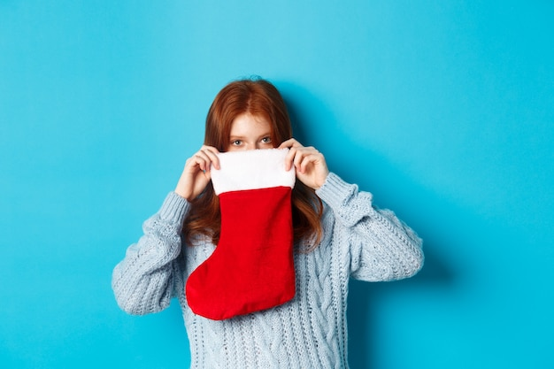 冬の休日とギフトのコンセプト。クリスマスの靴下の中を見て、青い背景に立って、目で笑って面白い赤毛の女の子。