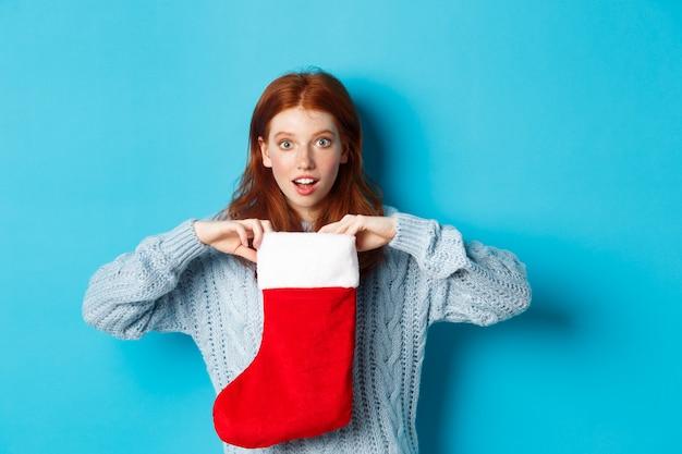 Зимние праздники и концепция подарков. смешная рыжая девушка выглядит удивленным, открытым рождественским чулком и улыбается, получая рождественский подарок, стоя на синем фоне.