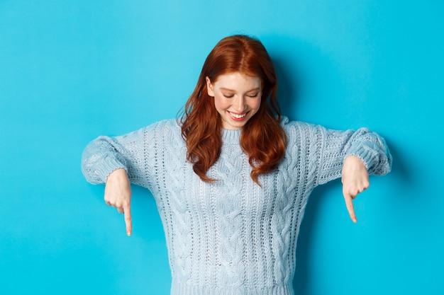 겨울 방학 및 사람들 개념. 스웨터에 밝은 빨간 머리 소녀, 손가락을 가리키고 파란색 배경 위에 서있는 로고에서 행복을 찾고