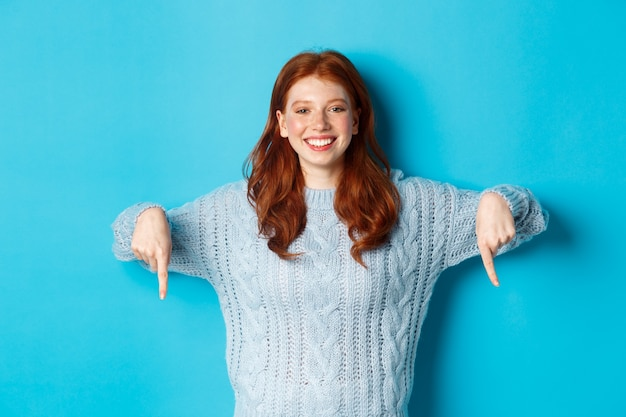 겨울 방학 및 사람들 개념. 아래로 손가락을 가리키는 스웨터에 쾌활 한 빨간 머리 여자 프로 모션, 파란색 배경을 보여주는 카메라에 기쁘게 미소.