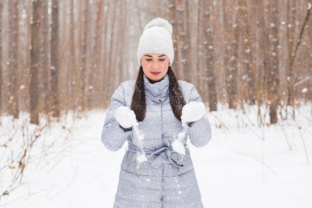 冬、休日、人々の概念-陽気な若い女性は冬の森を歩いて幸せです