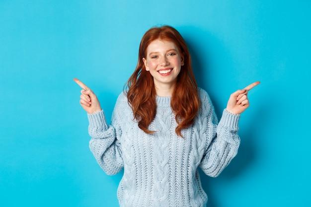 冬の休日と人々の概念。赤い髪、笑顔と横向きの指、広告を表示、青い背景の上に立っているかわいい十代の少女