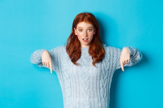 冬の休日と人々の概念。指を下に向けて、広告を表示し、青い背景の上に立っているかわいい10代の少女