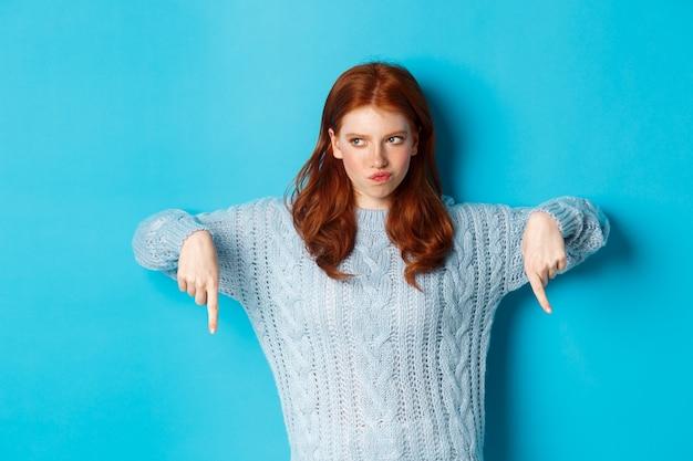겨울 방학 및 사람들 개념. 스웨터에 우유부단 한 빨간 머리 소녀 손가락 아래로 가리키고 생각, 의심을 가지고, 파란색 배경 위에 서