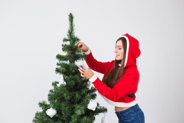 Зимние каникулы и люди концепция влюбленная пара, висящие украшения на елке в белой комнате
